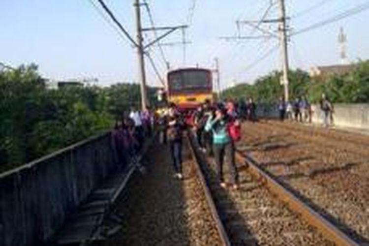 Sejumlah penumpang KRL yang turun dari kereta yang mereka tumpangi, Senin (25/5/2015) pagi. Hal ini terjadi akibat kereta berhenti terlalu lama menyusul adanya gangguan wesel di Stasiun Jakarta Kota.