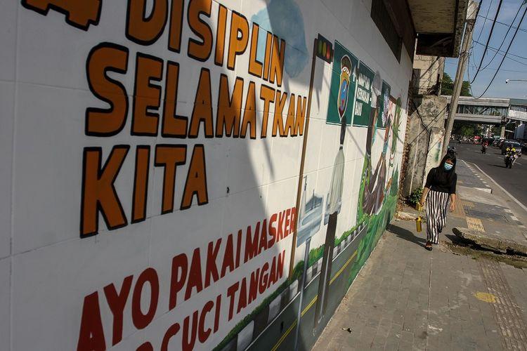 Warga melintas di dekat mural yang bertemakan pencegahan penyebaran COVID-19 di Jalan Stasiun Kereta Api Medan, Sumatera Utara, Rabu (3/2/2021). Mural adaptasi kebiasaan baru karya anggota Komunitas Mural Medan ini dibuat sebagai bentuk edukasi sekaligus sosialisasi penerapan protokol kesehatan kepada warga untuk selalu memakai masker guna mencegah penyebaran COVID-19. ANTARA FOTO/Rony Muharrman/hp.