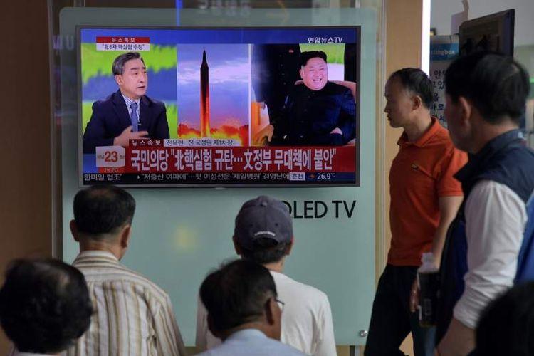 Warga kota Seoul menyaksikan di layar televisi berita uji coba keenam senjata nuklir Korea Utara, Minggu (3/9)