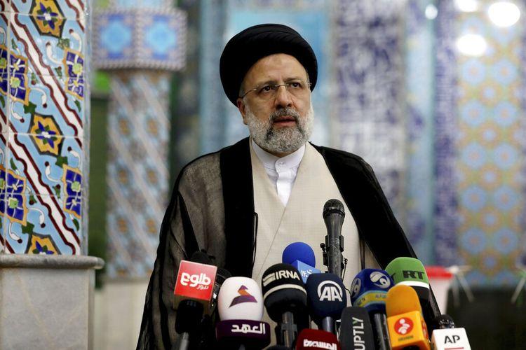 Calon presiden Iran Ebrahim Raisi melambai ke media setelah memberikan suaranya di tempat pemungutan suara di Teheran, Iran, Jumat (18/6/2021). Iran menggelar pemungutan suara dalam pemilihan presiden pada Jumat.