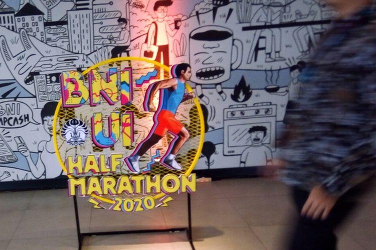 Seseorang hendak melintas di depan logo BNI UI Half Marathon 2020, pada Kamis (12/3/2020). Kompleks kampus UI Depok masih menjadi andalan lokasi acara. Di situ, lokasi yang kaya akan pepohonan bakal disterilkan dari kendaraan bermotor.