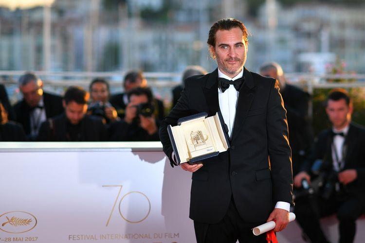 Aktor Amerika Joaquin Phoenix berpose dengan penghargaan yang diterimanya sebagai aktor terbaik dalam Festival Film Cannes 2017 di Cannes, Perancis, Minggu (28/5/2017).