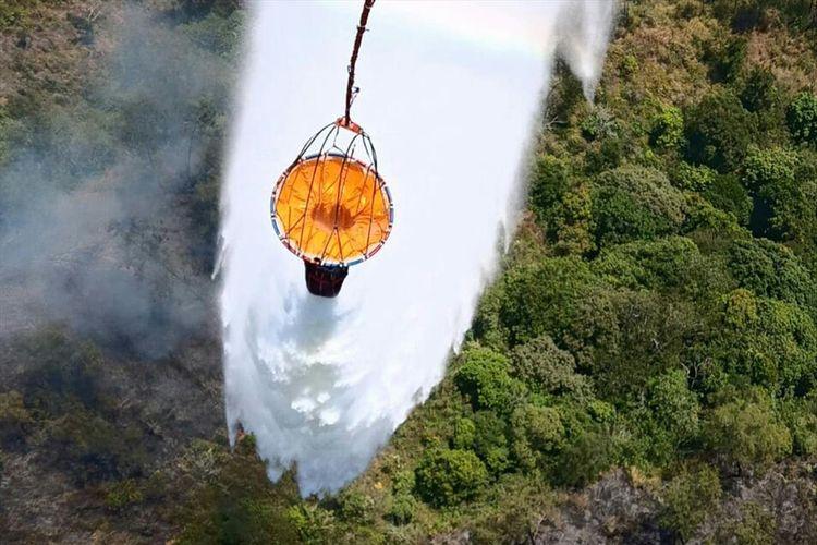 Operasi pemadaman kebakaran hutan melalui helikopter pengebom air di Gunung Arjuno, Jawa Timur, Minggu (4/8/2019)
