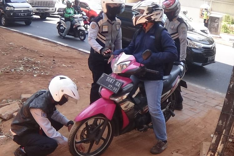Petugas Dishub lakukan sanksi cabut pentil kepada pengendara motor yang parkir dan memutar jalan di area hijau Jalan Doktor Satrio, Kuningan, Jakarta Selatan, (22/10/2019).