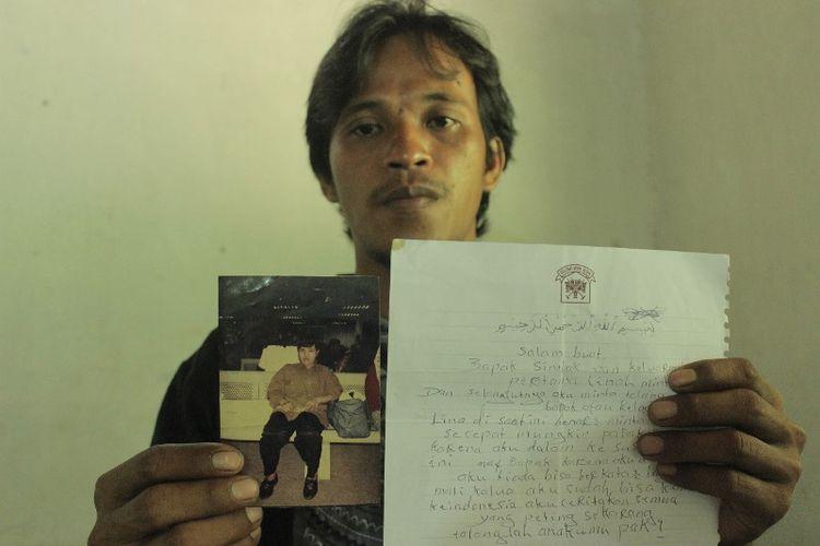 Parsin (33), warga RT 001 RW 003 Grumbul Glempang, Desa Petarangan, Kecamatan Kemranjen, Banyumas, Jawa Tengah, menunjukkan foto dan surat dari ibunya, Parinah (50), TKI yang diduga menjadi korban tindak pidana perbudakan modern di Inggris.