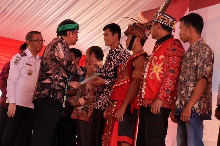 Menteri Agraria dan Tata Ruang, Sofyan Djalil memberikan sertifikat kepada salah seorang warga di Rumah Radangk, Pontianak, Kalimantan Barat, Rabu (24/4/2019).