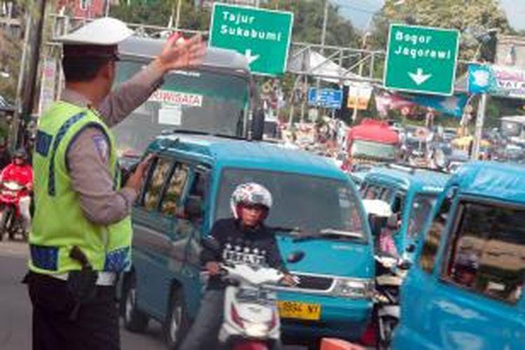Petugas Lalu Lintas Polres Bogor mengatur kendaraan yang melintas ke arah Puncak, Minggu (27/12/2015).