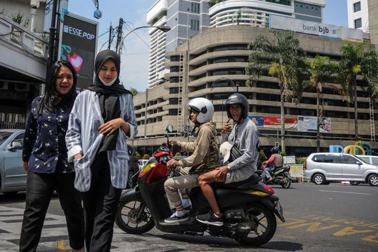 Pengguna kendaraan dan penyeberang jalan di Jalan Braga, Bandung, Jawa Barat, Selasa (14/07) yang tidak mengenakan masker.