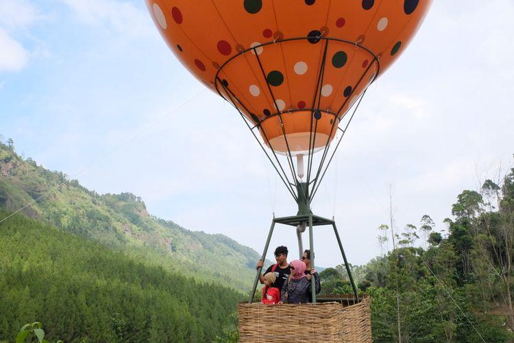 Pengunjung sedang berpose di wahana balon terbang The Lodge Maribaya, Bandung, Jawa Barat.