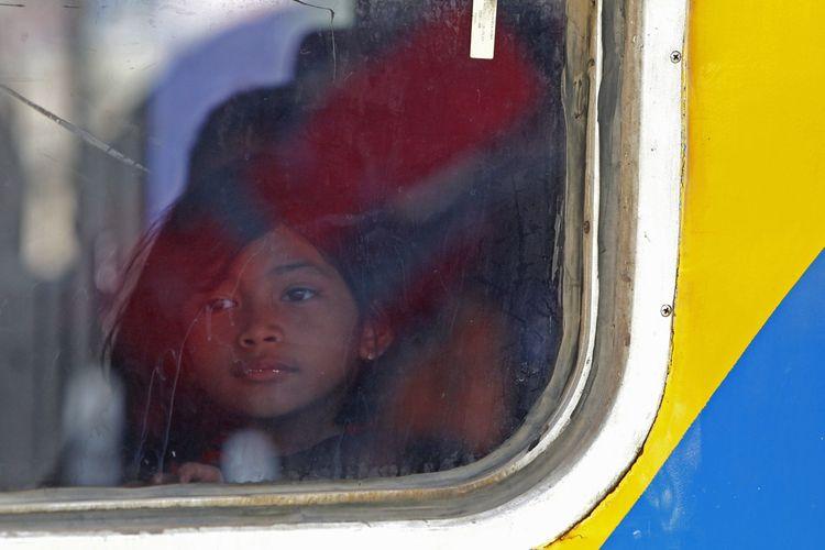 Seorang anak yang ikut mudik menunggu kereta diberangkatkan di Stasiun Pasar Senen, Jakarta, Senin (13/7/2015). PT KAI mempersiapkan sekitar 370 rangkaian kereta untuk mengakomodir 96.000 pemudik tiap harinya selama arus mudik dan balik.