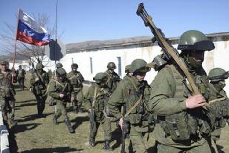 Seorang pria sambil membawa bendera Rusia menyambut rombongan pasukan bersenjata di desa Perevalne dekat ibu kota Crimea, Simferopol, Senin (3/3/2014).