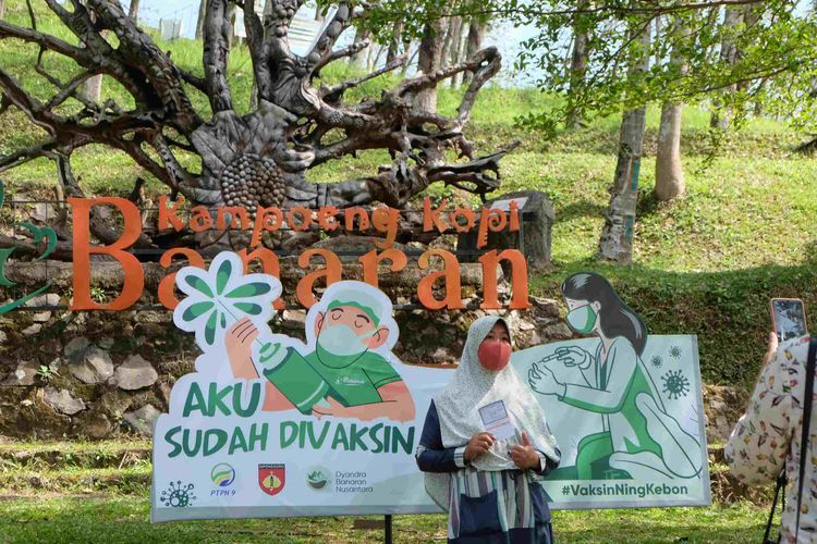 Peserta vaksinasi di Kampoeng Kopi Banaran menunjukan kartu tanda telah mendapat dosis kedua.