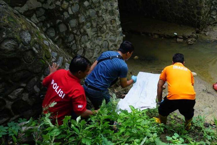 Petugas dari Polres Mojokerto Kota, melakukan identifikasi dan evakuasi terhadap jenazah bocah SD yang ditemukan di bawah jembatan Sungai Kedung Ungkal, di tepi hutan Kemlagi, Kabupaten Mojokerto, Jawa Timur, Kamis (30/1/2020).