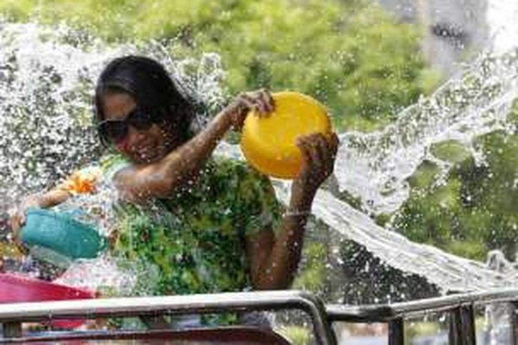 Seorang perempuan Thailand menyiramkan air ke badannya dalam acara perayaan Tahun Baru Thailand di Bangkok.