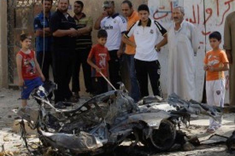 Warga melihat bekas serangan bom mobil di kawasan permukiman Husseiniyah, Baghdad, Irak, yang sebagian besar penghuninya adalah warga Syiah, Selasa (25/6/2013). Sementara di dekat kota Tuz Khurmato, sebelah utara Baghdad, dua bom bunuh diri menewaskan warga minoritas Syiah keturunan Turkmenistan.
