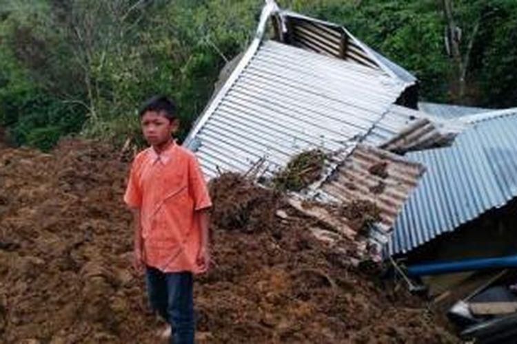 Junawan bin Wagiman (11), seorang anak yatim berdiri didepan rumahnya yang telah menjadi hancur akibat dihantam material longsor di Km 9 Peregen, jalur Isaq - Jagong, Kecamatan Linge, Kabupaten Aceh Tengah, Aceh, Sabtu (24/10) malam.