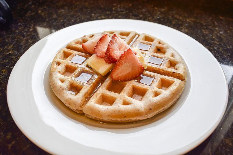 Ilustrasi waffle dengan maple syrup, butter, dan stoberi.