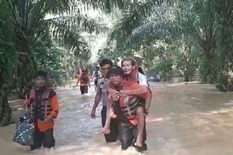Anggota Basarnas Pekanbaru, Guntur menggendong kakek Warjito (60) yang dievakuasi dari rumahnya terdampak banjir di Desa Pelanduk, Kecamatan Kunto Darussalam, Kabupaten Rohul, Riau, Senin (25/11/2019).