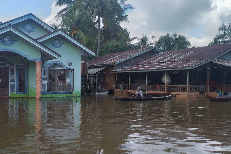 Seorang warga menggunakan perahu untuk beraktivitas di tengah banjir di Desa Buluh Cina, Kecamatan Siak Hulu, Kabupaten Kampar, Riau, Jumat (20/12/2019).