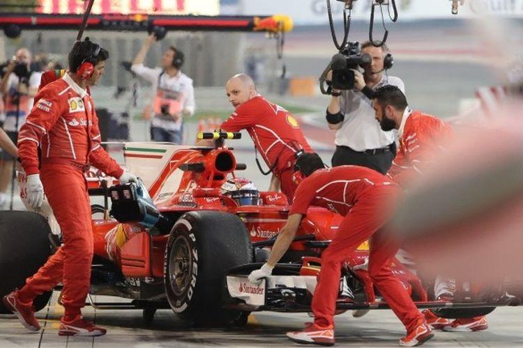 Pebalap Ferrari, Kimi Raikkonen, memasuki garasi timnya saat menjalani sesi latihan bebas GP Bahrain di Sirkuit Internasional Bahrain, Sakhir, Jumat (14/4/2017).