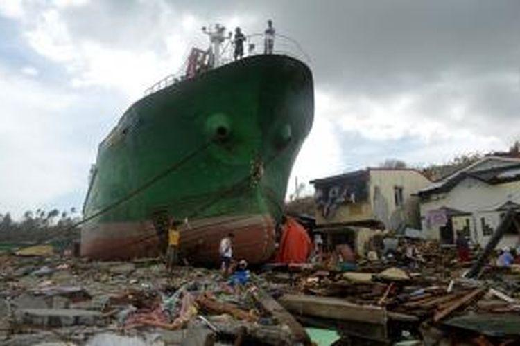 Warga berjalan-jalan dan melihat-lihat sebuah kapal yang terseret ke daratan di dekat kota Tacloban akibat sapuan topan Haiyan.