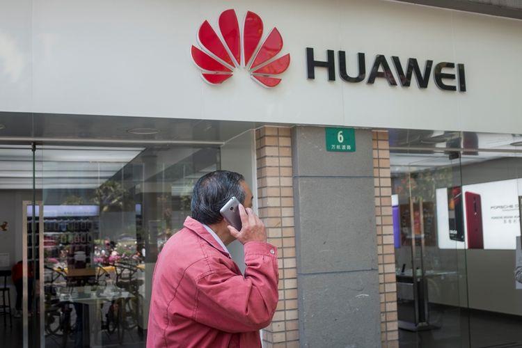 Warga menggunakan ponsel melintas di depan toko Huawei di Shanghai.