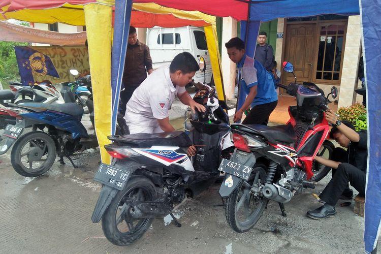 Para siswa terlihat antusias memperbaiki motor pengendara yang mogok di Jalan Raya Morowudi, Rabu (8/1/2020).