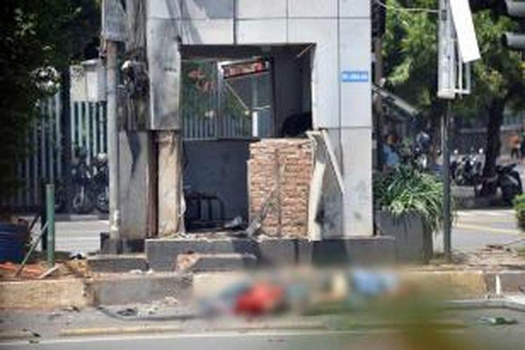 Dua jenazah terlihat di tepi jalan sebelah pos polisi yang rusak setelah ledakan menghantam kawasan Jalan MH Thamrin, Jakarta Pusat, 14 Januari 2016. Serangkaian ledakan menewaskan sejumlah orang, terjadi baku tembak antara polisi dan beberapa orang yang diduga pelaku.