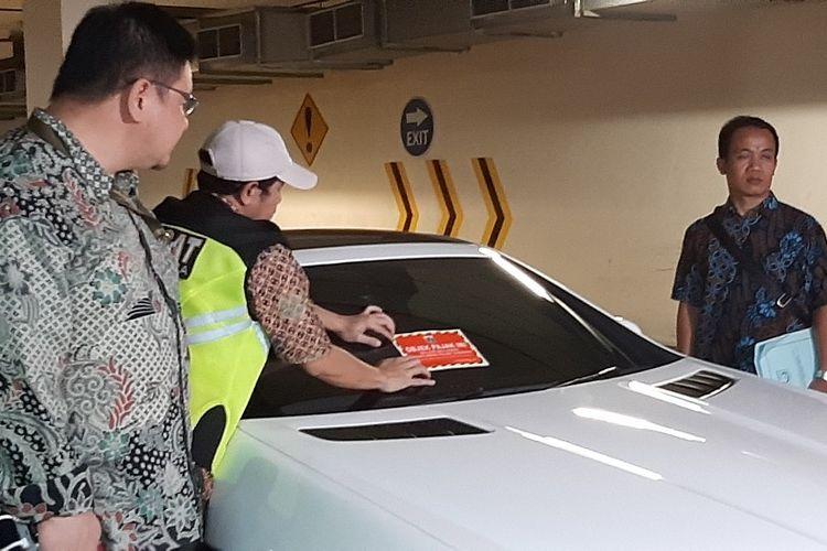 Petugas memasang stiker ke mobil yang belum dibayar pajaknya di Apartemen Regatta, Jakarta Utara, Kamis (5/4/2019).