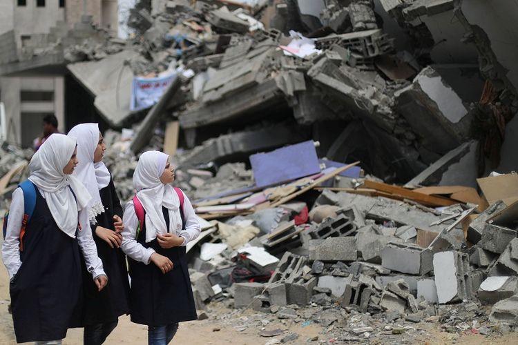 Pelajar Palestina di Gaza menyaksikan bangunan yang dihancurkan oleh serangan udara Israel di dekat sekolah mereka yang rusak, Selasa (7/5/2019). (REUTERS/Mohammed Salem)