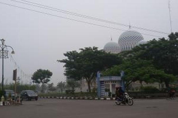 Warga melintas di depan Islamic Center Kota Lhokseumawe, Aceh yang diselimuti kabut asap, Minggu (25/10/2015)