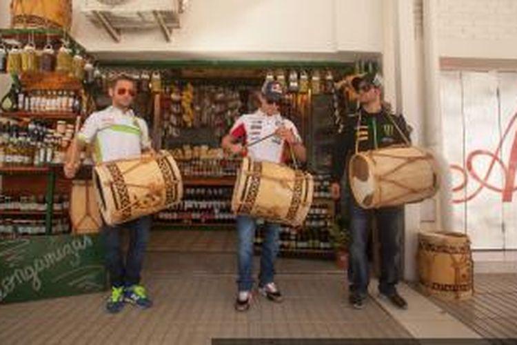 Pebalap MotoGP, Stefan Bradl (tengah), Alvaro Bautista (kiri), dan Cal Crutchlow, mencoba alat musik khas daerah Termas, saat melakukan kunjungan untuk uji coba di Sirkuit Termas de Rio Hondo, Argentina, Rabu (3/7/2013).