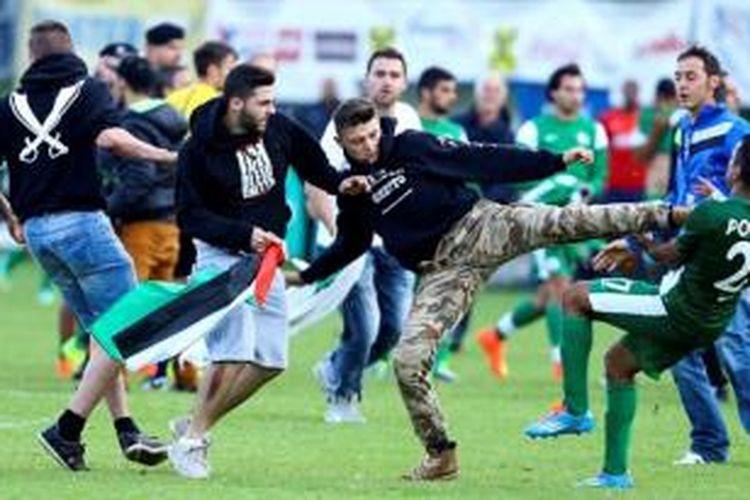 Seorang pria yang diduga berasal dari Turki masuk ke lapangan hijau kemudian menyerang seorang pemain klub Israel Maccabi Haifa dalam sebuah pertandingan persahabatan di Austria. Serangan ini diduga terkait operasi militer Israel ke Jalur Gaza yang sudah menewaskan ratusan orang.