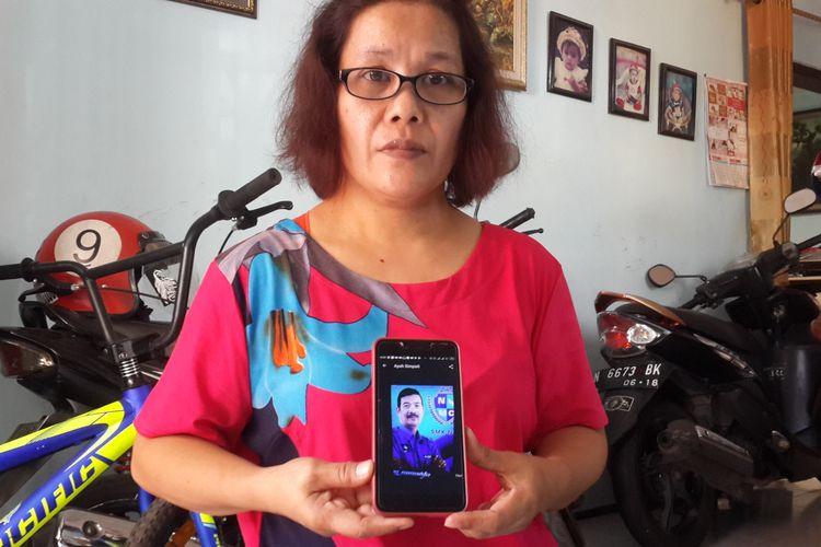 Dong Maria Boru Haloho saat menunjukkan foto suaminya Agus Susanto yang meninggal usai bertugas sebagai KPPS, Jumat (3/5/2019) di rumahnya di Jalan Tlogo Indah nomor 70 RT 06 RW 01 Kelurahan Tlogomas, Kecamatan Lowokwaru, Kota Malang