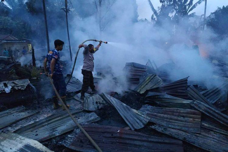 Petugas Polsek Lirik bersama damkar memadamkan api yang membakar tiga unit rumah akibat tersangka T (65) membakar rumahnya karena ribut dengan istrinya di Desa Jayapura, Kecamatan Lirik, Kabupaten Inhu, Riau, Rabu (26/8/2020).