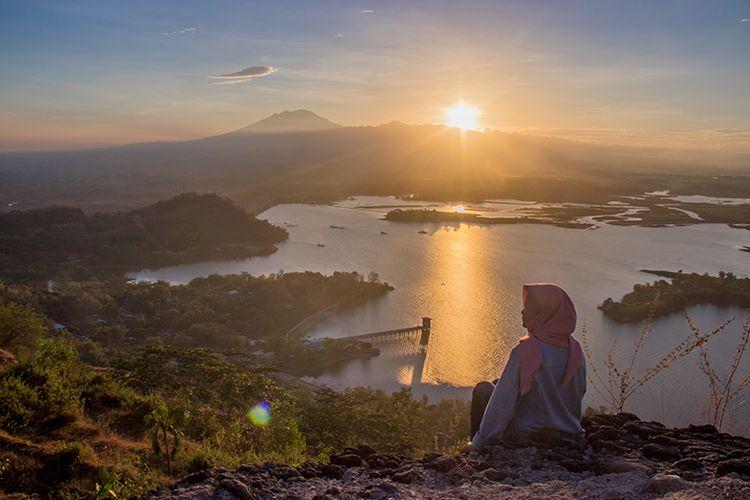 Seorang pengunjung berfoto dengan latar belakang keindahan matahari terbit di Watu Cenik, Wonogiri (13/06/2019).