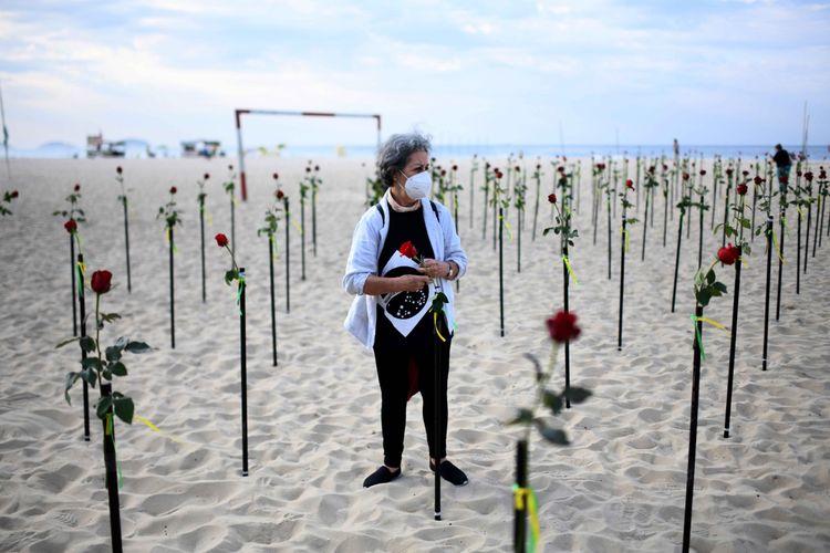 Seorang perempuan berdiri di antara bunga merah yang diletakkan LSM Rio de Paz di pantai Copacabana untuk memberikan penghormatan atas setengah juta kematian akibat Covid-19 di Brazil, di Rio de Janeiro, Brazil, Minggu (20/6/2021).