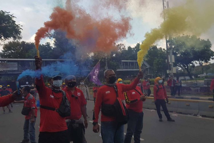Workers from the KASBI Labor Association fire multicolored smoke bombs and flares to signify the end of May Day protests on Saturday (1/5/2021).