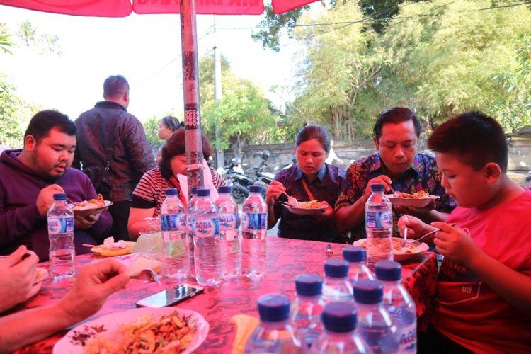 Wisatawan melahap sarapan di warung Nasi Campur Bali, Bu Weti, Pantai Segara Ayu, Sanur, Bali, Jumat (28/9/2018).