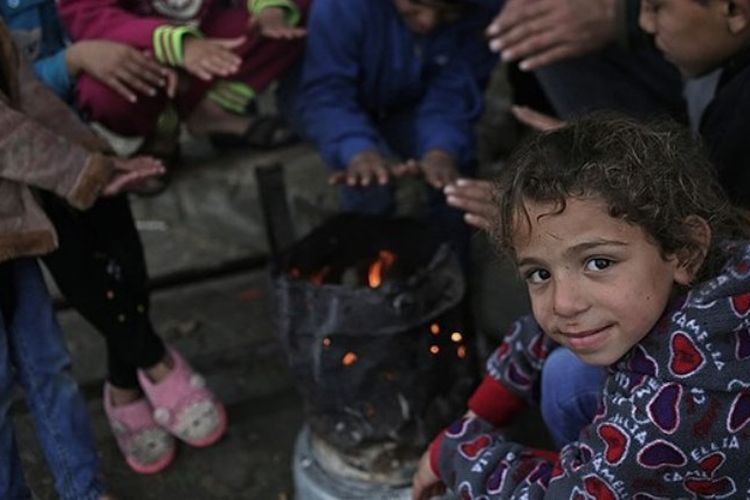 Anak-anak Palestina tengah menghangatkan diri di luar rumah mereka di Beit Hanun, sebuah kota yang terletak di utara Jalur Gaza (28/1/2018).