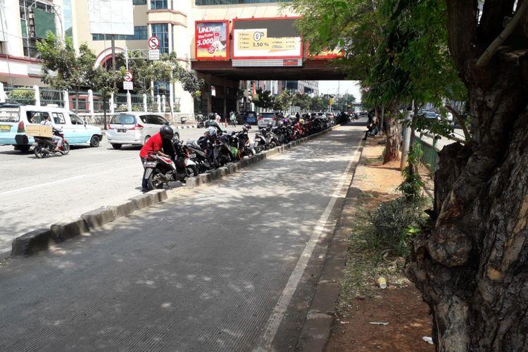 Sejumlah pengemudi ojek online tetap nekat memarkirkan kendaraannya di tepian jalur bus Transjakarta di Jalan Mangga Dua Raya, Jakarta Utara, tepatnya di depan ITC dan Mal Mangga Dua, Senin (7/5/2018).