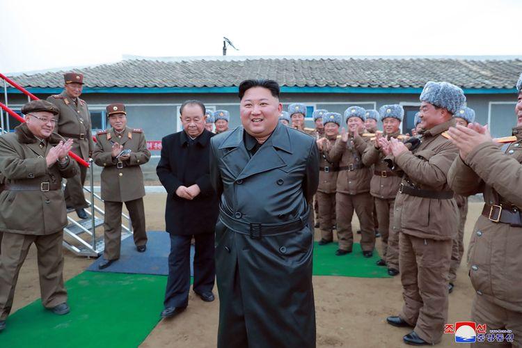 Gambar tak bertanggal yang dirilis kantor berita Korea Utara, KCNA, pada 29 November 2019 memperlihatkan Kim Jong Un mengawasi uji coba senjata terbaru. Kim yang mengenakan jubah warna hitam tersenyum dengan pasukan Korea Utara di sekelilingnya memberikan tepuk tangan.