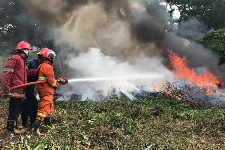 Anggota pemadam kebakaran Kota Depok, Jawa Barat memadamkan api yang berasal dari kabel yang terbakar di pinggir Jalan Raya Sawangan, Rangkapan Jaya Baru, Pancoran Mas, Kota Depok, Jawa Barat, Rabu (23/9/2020) siang.