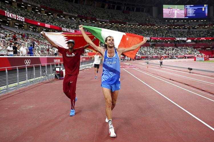 Peraih medali emas Mutaz Barshim, kiri, dari Qatar, dan Gianmarco Tamberi, dari Italia, merayakan kemenangan setelah berbagi emas setelah final lompat tinggi putra di Olimpiade Musim Panas 2020, Minggu, 1 Agustus 2021, di Tokyo, Jepang.