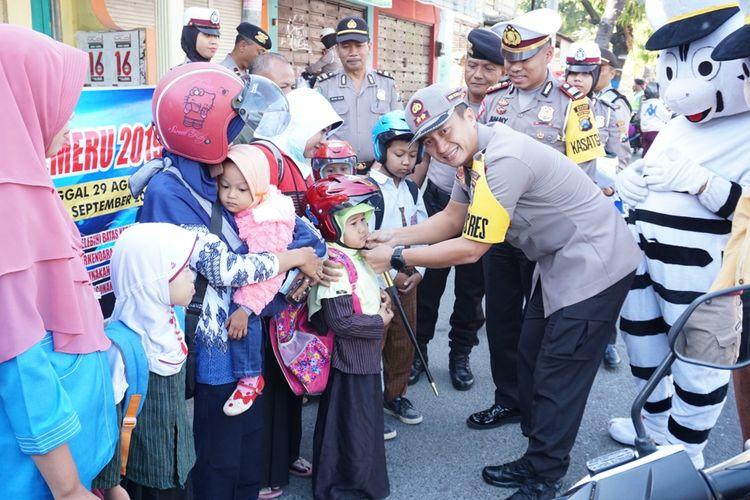 BERIKAN HELM--Kapolres Madiun, AKBP Ruruh Wicaksono memberikan helm gratis bagi anak-anak yang terjaring dalam operasi patuh 2019 di ruas jalan Madiun-Ponorogo, Kecamatan Dolopo, Kabupaten Madiun, Kamis ( 5/9/2019) siang.
