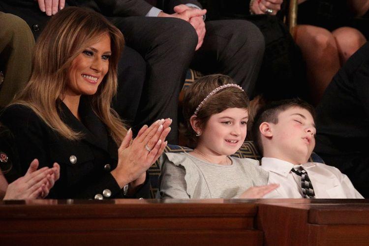 Ibu Negara AS, Melania Trump (kiri) duduk di samping gadir penyintas kanker, Grace Eline, dan Joshua Trump (kanan) yang tampak tertidur dalam agenda pembacaan pidato kenegaraan di US Capitol, Selasa (5/2/2019).