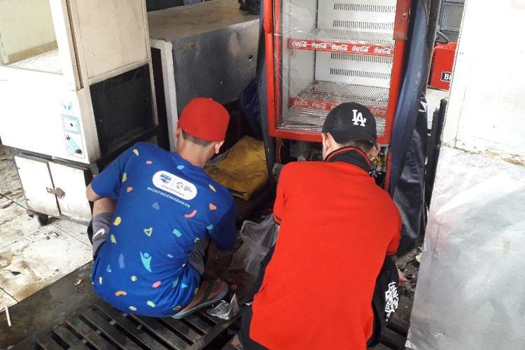Dua orang karyawan warung milik Rajab membereskan sisa-sisa pecahan kaca dari lemari es yamg rusak akibat kerusuhan pada Rabu (22/5/2019) kemarin