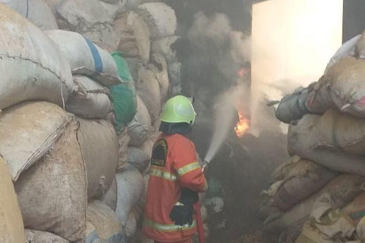 Petugas berupaya memadamkan api yang membakar gudang UD Rahayu Lestari.
