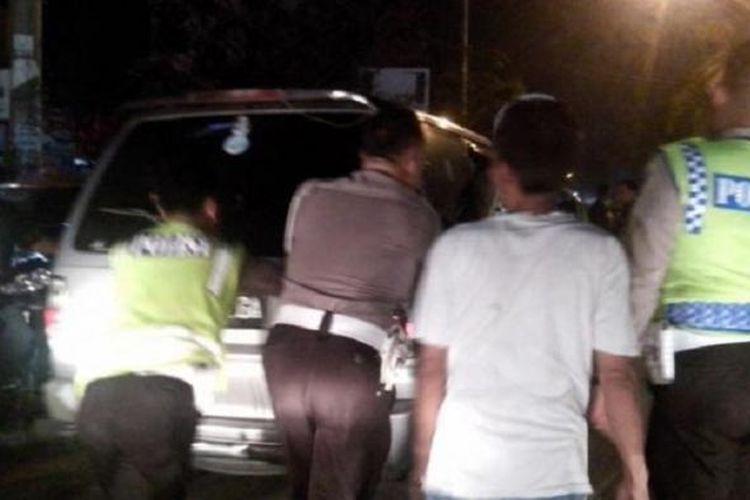 Petugas kepolisian mendorong mobil yang diduga penyebab kemacetan di Jalan Jamin Ginting, Selasa (30/6/2015) malam