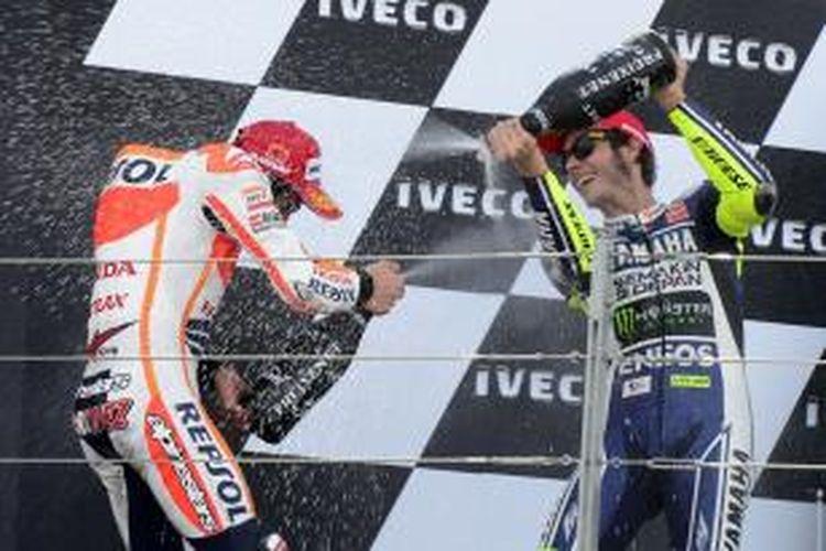 Pebalap Yamaha asal Italia, Valentino Rossi (kanan) yang finis ketiga pada GP Aragon, merayakan suksesnya di atas podium MotorLand, dengan saling menyemprotkan champagne dengan juara balapan, Marc Marquez dari Spanyol.